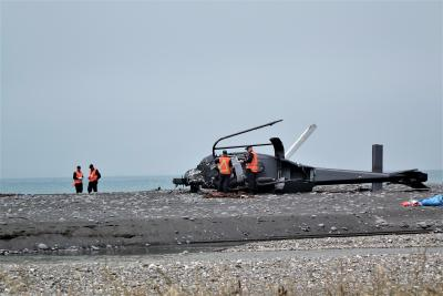Photo - TAIC investigators inspect the helicopter wreckage on the beach